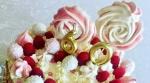 Dekoration einer Torte in weiß, rosa und gold ist sichtbar. Die Torte ist mit zwei Baiserlollis , frischen Himbeeren, Raffaelokugeln und Baiserdrops dekoriert. in Der Mitte befindet sich eine goldene Kerze aus den Zahlen 6 und 0