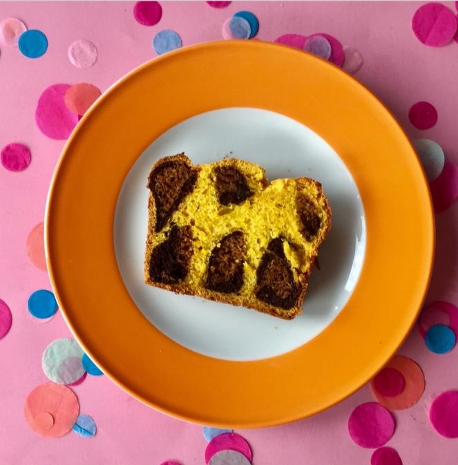 Auf einem weißen Teller mit dickem orangenen Rand befindet sich eine Scheibe Kuchen mit braunen Leopardenmuster. Der Teller befindet sich auf einem rosa Untergrund mit bunten Konfettis dekoriert.