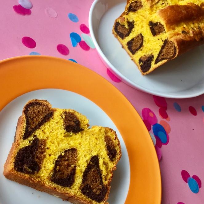 Hinter dem weißen Teller mit dicken orangenen Rand steht eine weiße Kuchenplatte mit dem Kastenkuchen. Der Anschnitt im Leopardenmuster ist sichtbar. Auf dem weiß-orangenen Teller liegt ein Stück Leopardenkuchen.