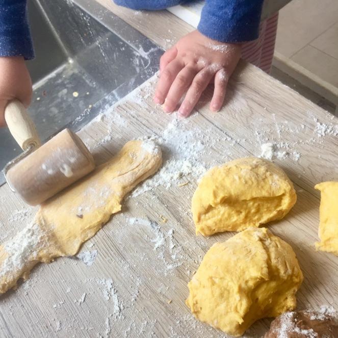 Auf einer bemehlten Arbeitsfläche rollen zwei Kinderhände eine helle Teigkugel zu einem Streifen aus. Auf dem Bild sind noch 3 weitere Kugeln und eine Spüle zu sehen.