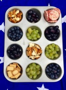Ein Muffinbackbleck gefüllt mit Blaubeeren, blauen und grünen Weintrauben, Keksen und anderen Knabbereien auf einer blauen Picknickdecke mit weißen Sternen