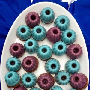 Minigugelhupfs mit lilaner und hellblauer Glasur auf einem weißen Kuchenteller auf einer blauen Picknickdecke mit weißen Sternen.