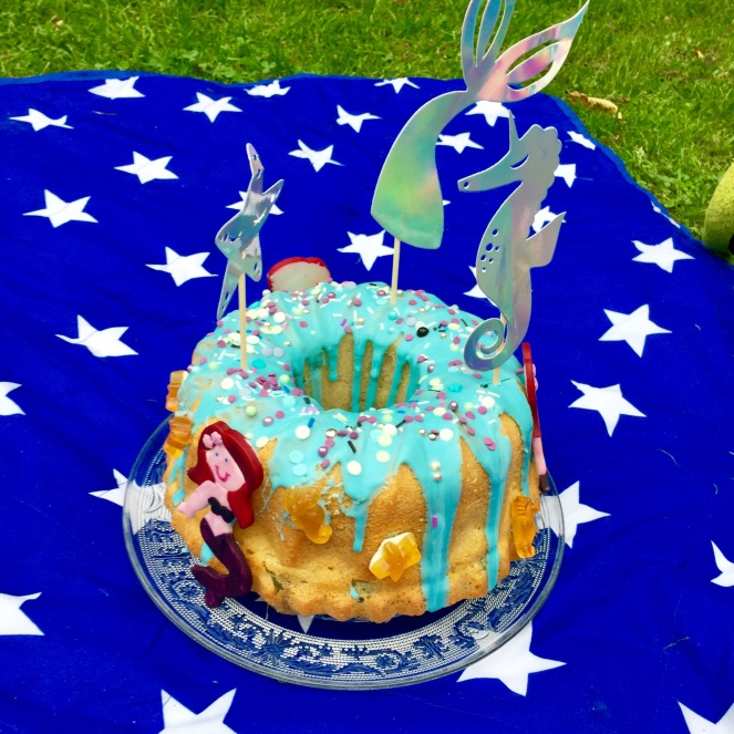Ein Gugelhupf dekoriert mit Türkisen Zuckerguss und lila-weißen Zuckerperlen mit Meerjungfrauen aus Fondant an der Seite und Papiercaketoppern aus glänzendem Material in Seestern-, Seepferdchen- und Meerjungfrauflossenform auf einer blauen Picknickdecke mit weißen Sternen auf einer grünen Wiese.