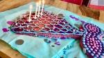 Eine aus einem lila Blechkuchen ausgeschnittene Meerjungfrauenschwanzflosse mit hellblauen gemalten Flossen und Smarties dekoriert. In Lila, hellblau, pink gehalten mit 4 weißen, brennenden Kerzen auf einer hellblauen Servierte auf einem Holztisch.