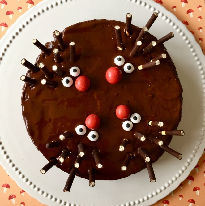Ein Schokoladenkuchen mit vier kleinen Igeln gestaltet aus einer roten Nase aus M und Ms, Zuckeraugen und Micadostäbchen als Stacheln auf einer weißen Kuchenplatte auf einem Papieruntergrund mit aufgedruckten Pilzen.