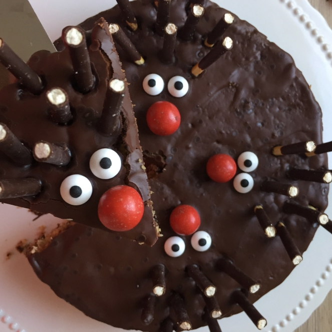 Der Schokolade-Nuss-Kuchen mit Igeln aus M und Ms für die Nase, Zuckeraugen und Micadostäbchen für die Stacheln dekoriert wurde angeschnitten und eine Stück wird auf dem Kuchenheber erhöht gen Kamera gehalten.