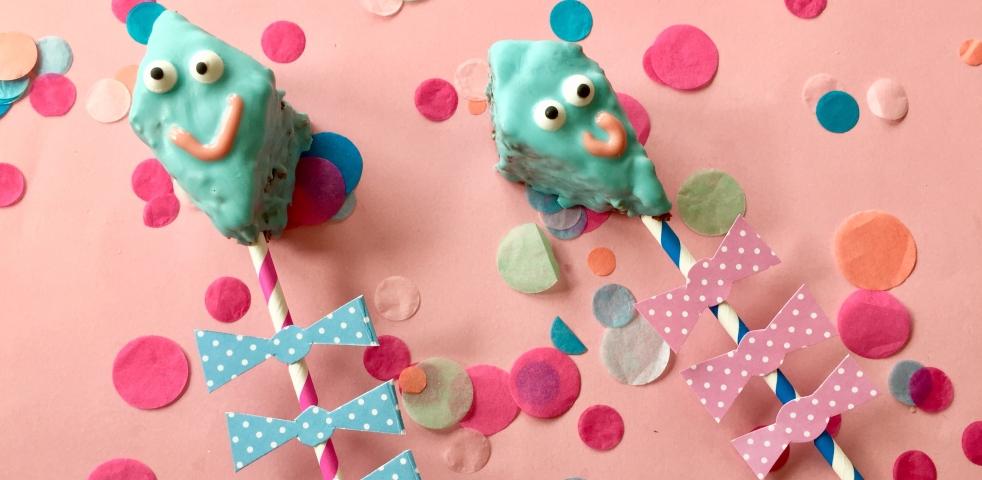 Hellblaue rautenförmige Drachen-Cakepops auf Papierstrohhalme gesteckt.
