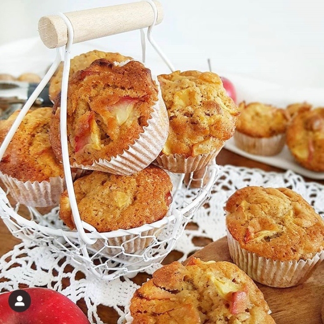 Goldbraune Apfelmuffins in einem Körbchen und verschiedenen Kuchenplatten auf einem Tisch arrangiert.