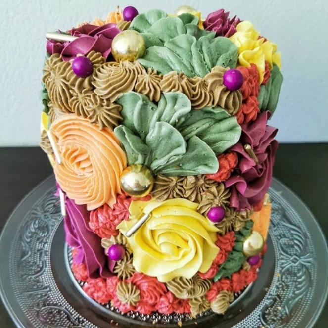 Eine stöckige hohe Torte, die mit Buttercreme in Herbstfarben und verschiedenen Spritztechniken und großen Dekoperlen dekoriert ist auf einem Glasteller vor neutralem Hintergrund.