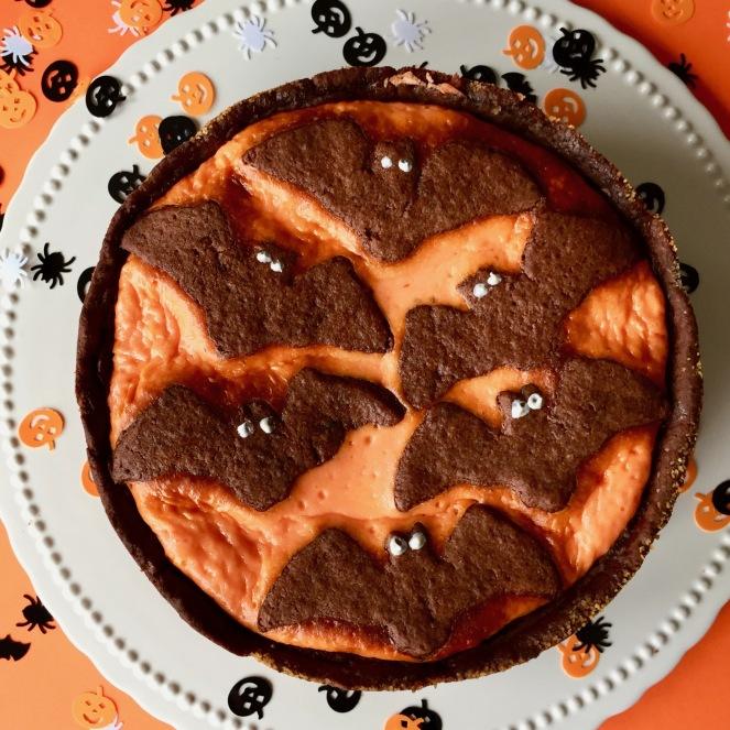 Ein Halloween Flatlay eines Russischen Zupfkuchens, dessen Füllung orange eingefärbt ist und mit braunen Teigfeldermäusen dekoriert ist. Auf einer weißen Tortenplatte auf orangenem Hintergrund dekoriert mit Halloween Streugut.