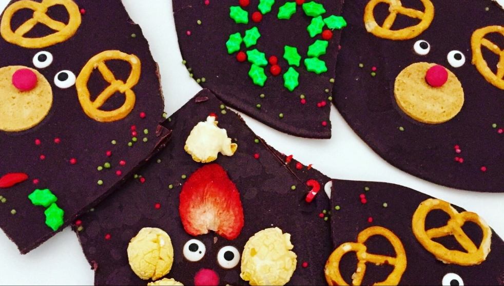 Auf dem Bild ist dunkelbraune Bruchschokolade mit weihnachtlichen Motiven dekoriert zu sehen - einem Mistelkranz, Rentieren und einem Nikolaus